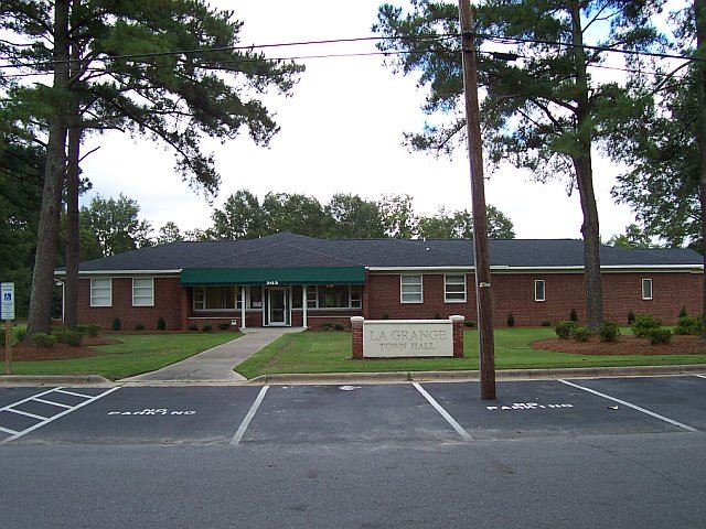 A view of the La Grange Town Hall from the street. Trees are visible, as well as a green awning.