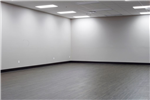 An empty room with grey floors and white walls.